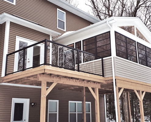 Custom deck and sunroom with glass railings