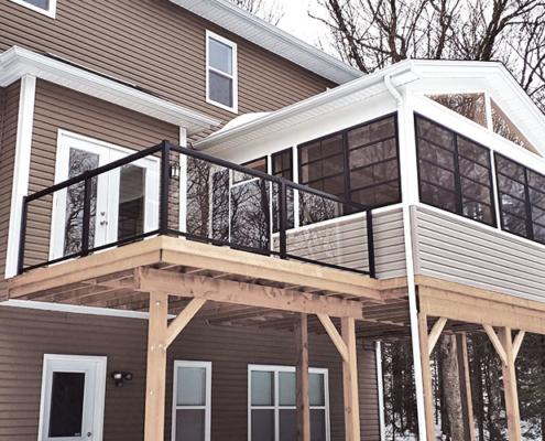 Custom deck and sunroom with glass railings